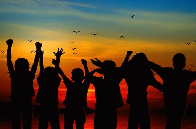 Jubelnde Kinder vor buntem Himmel
