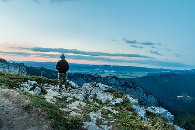 Mann auf Berg vor Himmel